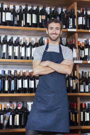 Portrait of confident salesman standing arms crossed in wine shop
