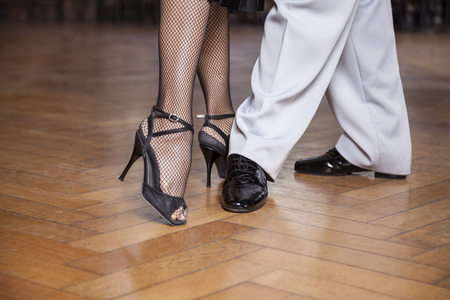 argentina dance: Low section of male and female tango dancers performing parallel walk in restaurant