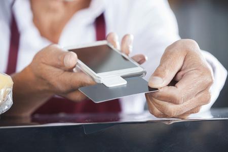 Immagine potata di venditore strisciata di carta di credito sul cellulare in un negozio di formaggi photo
