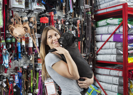 petshop: Smiling female customer looking away while carrying French Bulldog in store