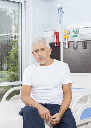 healthcare facilities: Portrait of thoughtful senior man sitting on bed at rehab center
