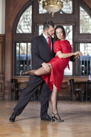 sensuous: Full length of male and female sensuous partners performing high leg wrap in restaurant Stock Photo