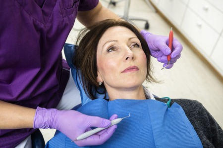 scaler: High angle view of female dentist examining patient with tools in clinic