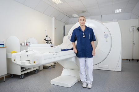 Retrato de cuerpo entero de radiólogo mujer joven de pie por la máquina de resonancia magnética en la clínica