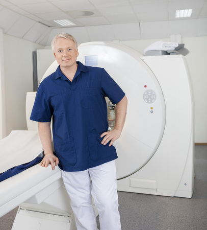 axial: Portrait of confident radiologist leaning on MRI machine in hospital Stock Photo