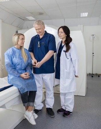 computer tomography: Full length of mature colleagues and patient with digital tablet before MRI scan in hospital