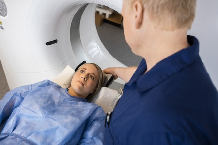 axial: High angle view of male radiologist preparing female patient for MRI scan in hospital