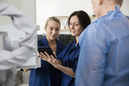 digital tablet: Female radiologists using tablet computer by patient in hospital