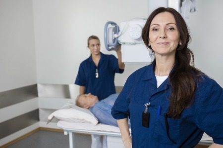 imaging: Portrait of mature doctor with hands on hip smiling while colleague taking patients xray in hospital Stock Photo