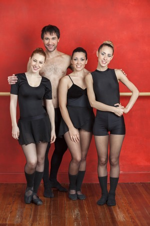 barre: Full length portrait of male and female ballet dancers standing against red wall in studio