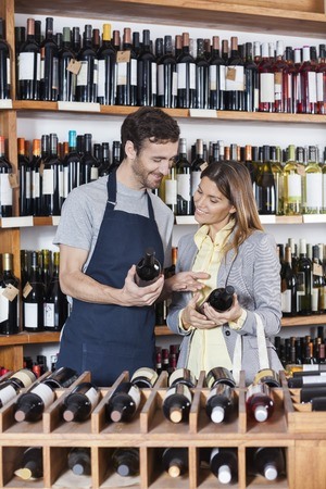 selling service smile: Young salesman discussing over wine bottles with female customer in shop