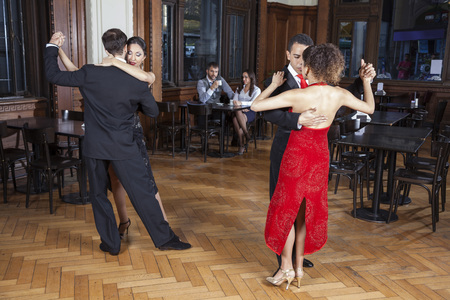 fashion clothing: Full length of male and female tango dancers performing while couple dating in restaurant