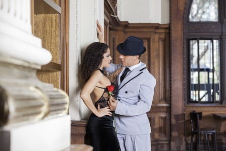 sensuous: Young tango dancer holding rose while looking at sensuous female partner in restaurant Stock Photo