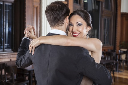 argentina dance: Portrait of happy woman performing tango with man in restaurant Stock Photo