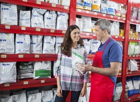 petshop: Smiling salesman assisting female customer in buying pet food at shop