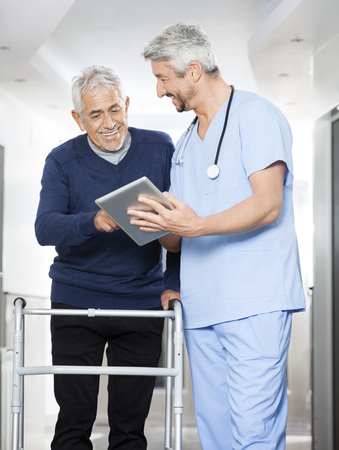 mobility nursing: Mature physiotherapist showing reports on tablet computer to senior man in rehab center Stock Photo