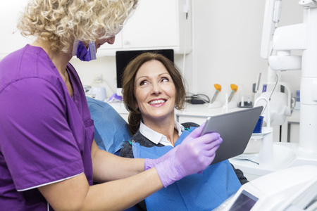 hygienist: Assistant showing report to happy female patient on digital tablet in dentistry Stock Photo
