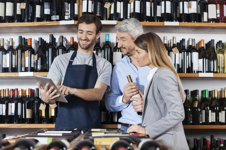 store keeper: Smiling young salesman showing wine information to customers on digital tablet in shop
