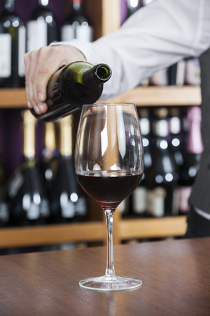 Cropped image of bartender pouring red wine in glass at counter Stock Photo