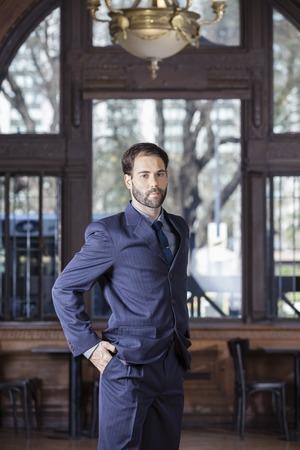 hands in pocket: Portrait of confident male tango dancer standing with hands in pockets in restaurant