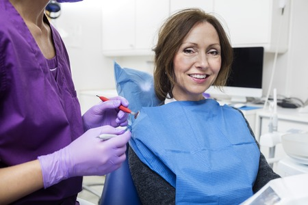 Portrait of smiling female patient by dentist holding tools in clinic Stock Photo