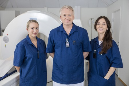 imaging: Portrait of confident medical team smiling while standing by MRI machine in hospital