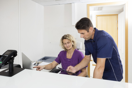 Male and female dentists using computers at reception desk in hospital