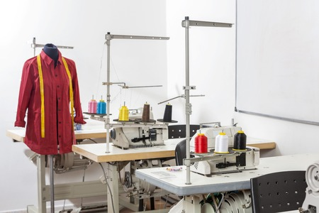 fashion design: Shirt on mannequin by workbenches in sewing factory