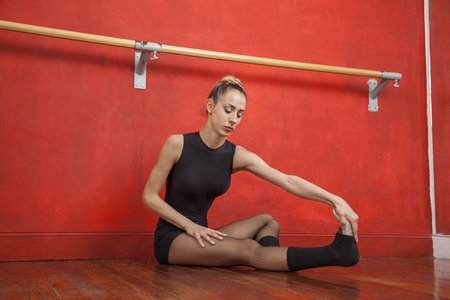 Full length of young female ballet dancer stretching on floor in rehearsal room