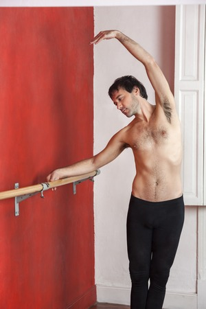 ballet hombres: Sin camisa bailarina de ballet masculino practicando en barra contra la pared en el estudio de danza Foto de archivo