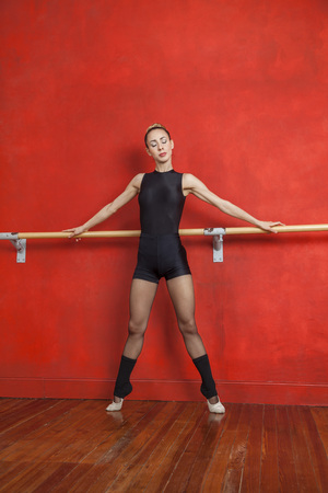 barre: Full length of confident ballerina performing at barre against red wall in dance studio