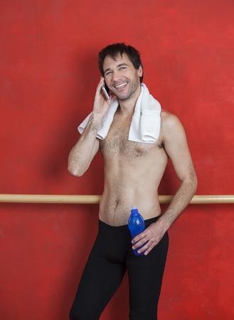 ballet hombres: instructor de ballet feliz que usa el teléfono inteligente mientras sostiene la botella de agua en el estudio de danza