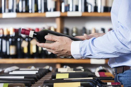 shop keeper: Midsection of male customer holding wine bottle in shop
