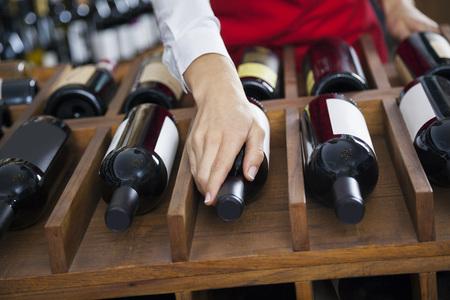 bottle of wine: Cropped image of mid adult saleswoman arranging wine bottles in rack at shop
