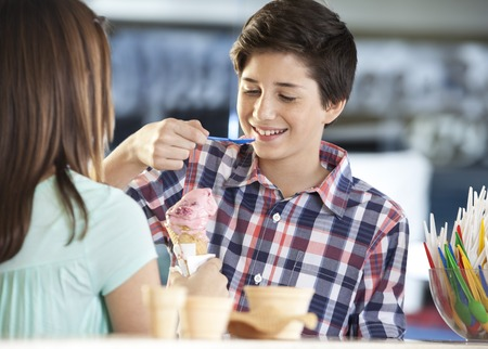 gelati: Smiling boy having strawberry ice cream while standing with sister in parlor