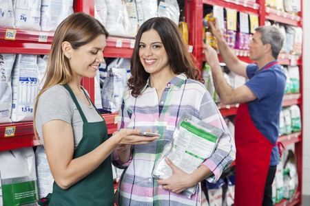 associates: Portrait of female customer making payment to saleswoman in pet shop Stock Photo