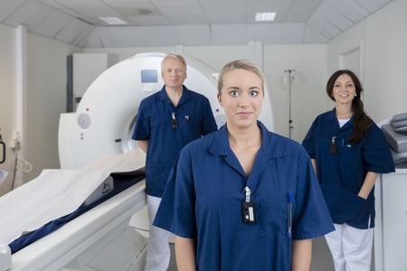 axial: Portrait of female doctor with colleagues standing by MRI machine in hospital Stock Photo
