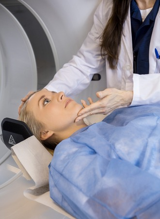 mri scan: Midsection of mature female doctor adjusting patients face before MRI scan in hospital Stock Photo