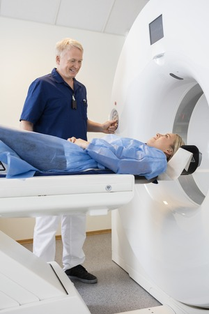 medical scanner: Smiling male professional looking at patient undergoing CT scan in hospital Stock Photo
