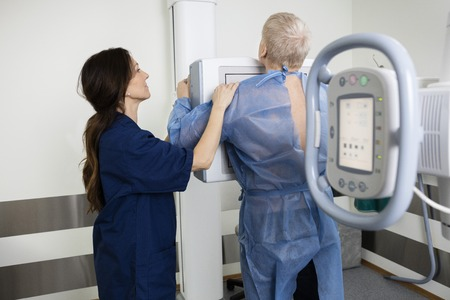 Mature female radiologist taking xray of man in hospital