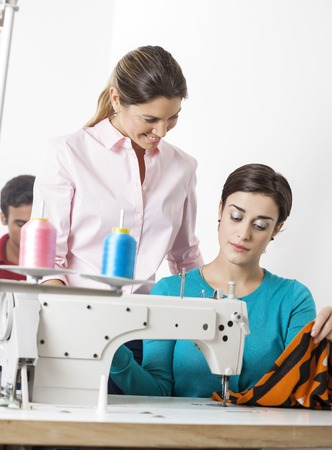 modiste: Smiling female tailor looking at colleague stitching in sewing factory