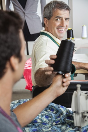 Happy mature tailor giving thread spool to male colleague in sewing factory