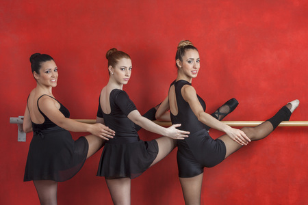 barre: Portrait of confident young ballerinas practicing at barre against red wall in studio