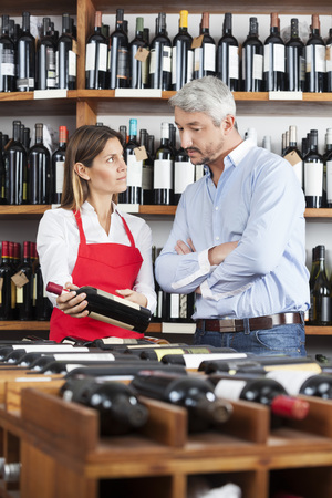 selling service smile: Mid adult saleswoman showing wine bottle to male customer in shop Stock Photo