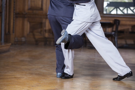 Low section of male tango dancers performing gancho step in restaurant Stock Photo