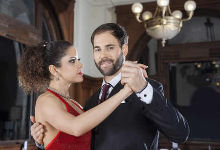 Portrait of male Argentine tango dancer performing gentle embrace step with partner in restaurant