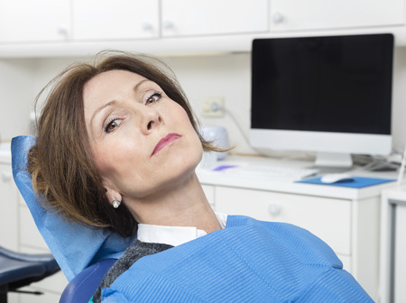 oral communication: Portrait of mature female patient sitting at dentists clinic