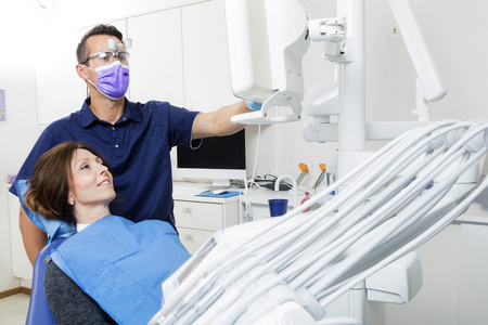 Mid adult male dentist explaining xray to female patient in clinic Stockfoto