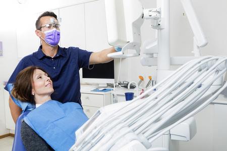 Mid-volwassen mannelijke tandarts die xray voor vrouwelijke patiënt in kliniek legt Stockfoto - 64972082