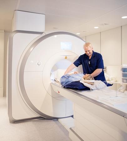 mri scan: Mature doctor preparing woman for MRI scan in laboratory Stock Photo